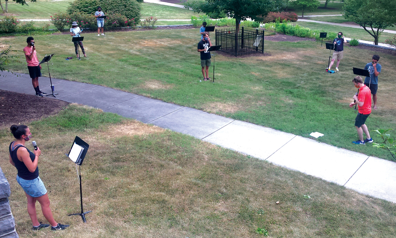 Eastern Mennonite University music professor Ben Bergey, right, and a group of student volunteers test equipment for choral practice in front of Lehman Auditorium. The singers wore masks, were positioned 12 feet apart, and used wireless microphones.