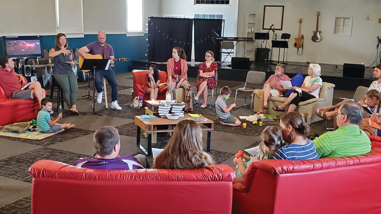 """Journey Mennonite Church's Yoder, Kan., campus worships in mid-June in a """"living room"""" setup with families sitting by household under COVID-19 distancing guidelines. — Journey Mennonite Church"""