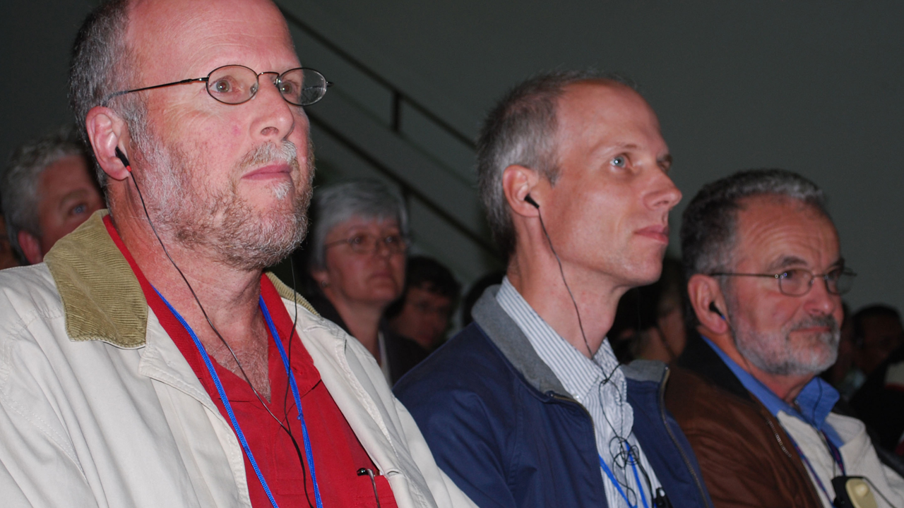 Past Editors: At the Mennonite World Conference assembly at Asuncion, Paraguay, in 2009, three editors whose publications preceded Anabaptist World listen to a speech. From left are Gordon Houser, editor of the GC version of The Mennonite, 1992-1998, and the MC USA version of The Mennonite, 2015-2020; Paul Schrag, editor of Mennonite World Review, 1996-2020; and J. Lorne Peachey, editor of Gospel Herald, 1990-1998, and the MC USA version of The Mennonite, 1998-2000 — Anabaptist World