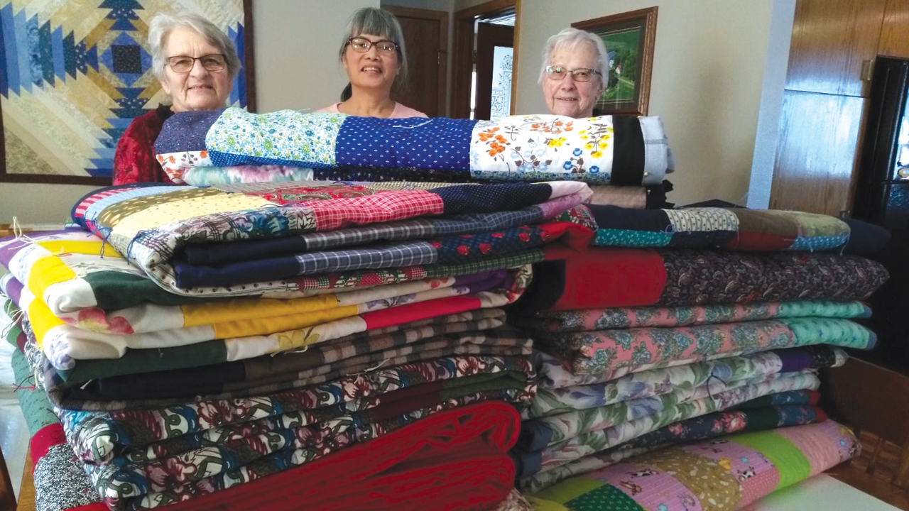 Eva Harder, left, completed her 100th comforter for Mennonite Central Committee on Aug. 19. Here she is joined by two women from First Mennonite Church in Mountain Lake, Minn., who helped tie some of the comforters, Pratoomporn Harder and Erna Johnson (who recently turned 84 and has made more than 30 comforters for MCC this year). — Gordon Harder