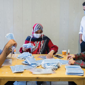 Ashkan Taghipour, standing, director of the Moms Against Poverty partner non­governmental organization in Tehran, Iran, supervises staff and volunteers repackaging masks sent by Mennonites. — Doug Hostetter