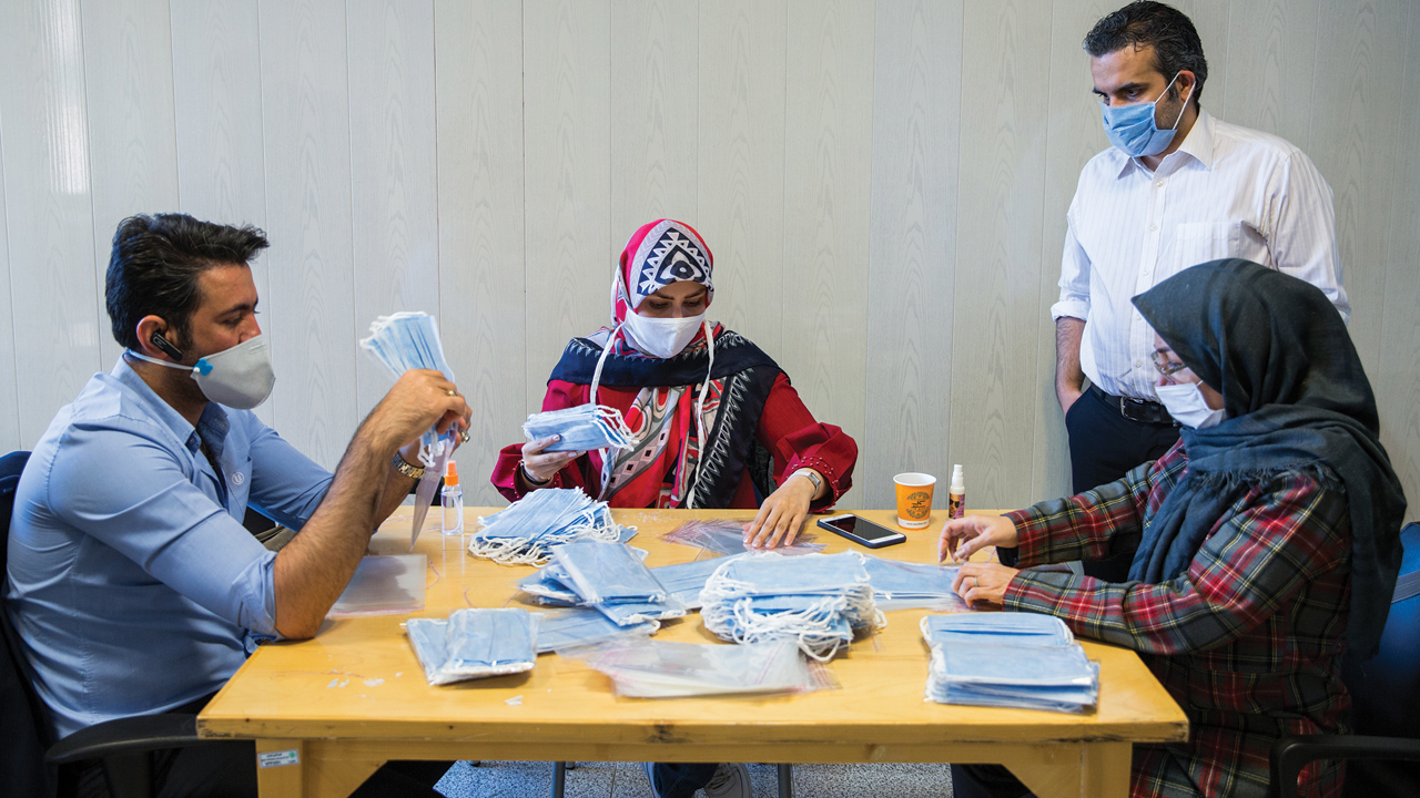 Ashkan Taghipour, standing, director of the Moms Against Poverty partner nongovernmental organization in Tehran, Iran, supervises staff and volunteers repackaging masks sent by Mennonites. — Doug Hostetter