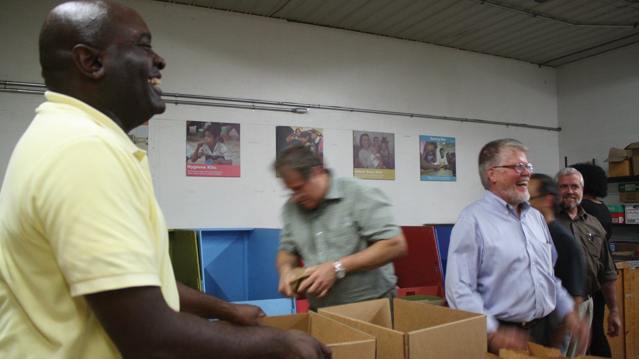 The mood was jovial as former MCC U.S. board member Leonard Dow, left, helped pack prisoner care kits in 2017 at the MCC East Coast Material Resources Center in Ephrata, Pa. Dow, other MCC U.S. board members and MCC staff, including MCC U.S. executive director J Ron Byler, right foreground, packed 100 kits of personal items for people who were incarcerated or who were participating in re-entry ministries after leaving prison in the greater Philadelphia area. — Jill Steinmetz/MCC
