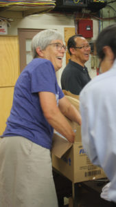 "Ann Graber Hershberger and MCC U.S. board member Sunoko Lin (back) of Lake Balboa, Calif., helped to pack boxes of prisoner care kits in 2017 at the MCC East Coast Material Resources Center in Ephrata, Pa. Hershberger will be acknowledged and blessed as the next MCC U.S. executive director at ""Celebration 2020: MCC at 100"" Oct. 17. — Jill Steinmetz/MCC"