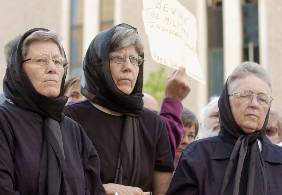 In this July 25, 2003, file photo, Dominican nuns, from left, Ardeth Platte, Carol Gilbert and Jackie Hudson listen to speakers before addressing a crowd outside the federal courthouse in downtown Denver. The women were convicted in April 2003 of obstructing the national defense and damaging government property for swinging a hammer at the silo and smearing their blood on it in the form of a cross. (AP Photo/David Zalubowski, File)