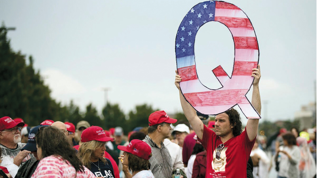 In this Aug. 2, 2018, photo, David Reinert holds a Q sign while waiting in line with others to enter a campaign rally with President Trump in Wilkes-Barre, Pa. — Matt Rourke/AP