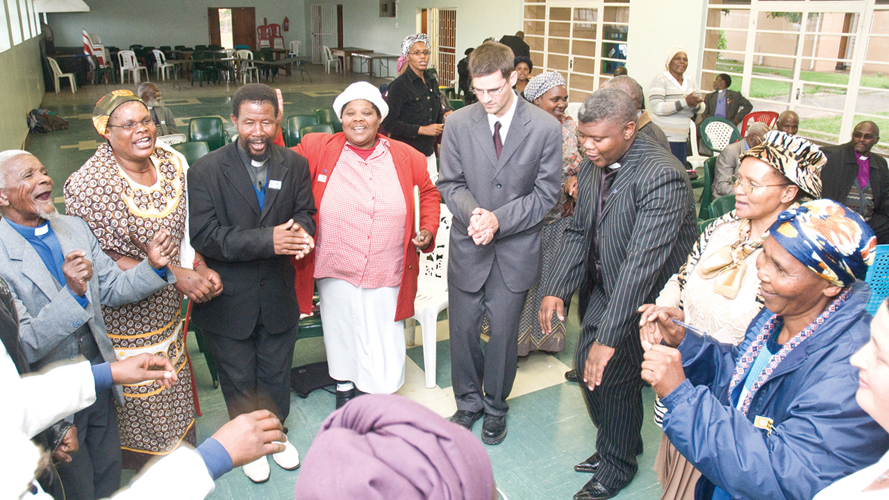 Amos Sobambela, M.N. Madikane, E.S. Simanga, Olga N.N. Dubula, Joe Sawatzky, Reuben Mgodeli, Mavis Tshandu, Miriam Nompumelelo Dokolwana and Anna Sawatzky sing and dance at Bethany Bible School in May 2009 in Mthatha, South Africa. — Ryan Miller/MMN