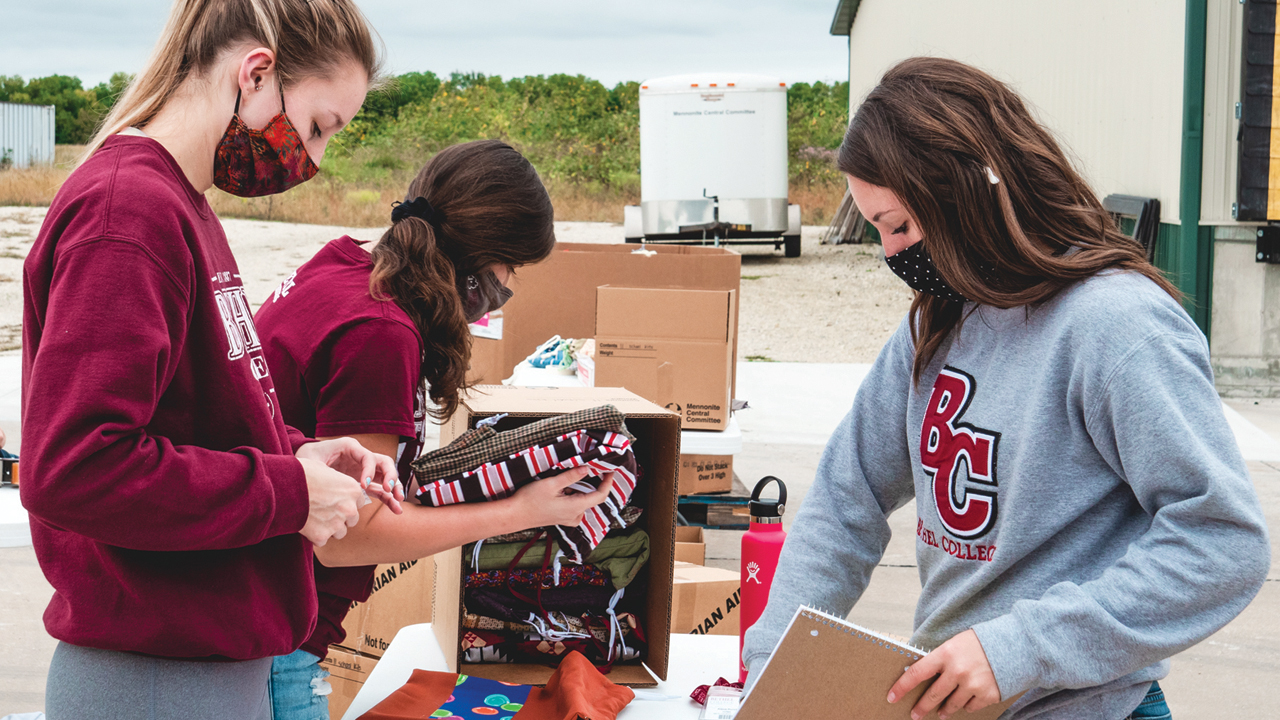 Bethel College students Julie Wilhite, Grace Lumpkins and Alexa Burch pack school kits at Mennonite Central Committee Central States on Sept. 23 during the college's annual Service Day. — Taylor Brown/Bethel College