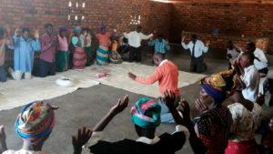 Members of the Mennonite Brethren Church in Malawi pray in September for the Mennonite Brethren Church of India. — International Community of Mennonite Brethren
