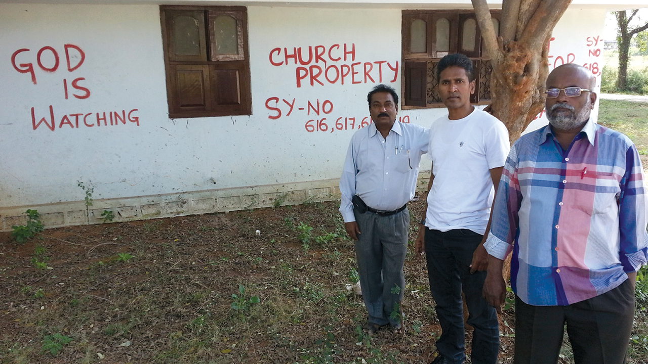 Members of the ad hoc committee for the General Council of MBCI, including Paul Gandham, center, painted warnings on the walls of Shamshabad Mission Compound and Bible College in 2013 after they say MBCI President P.B. Arnold made an illegal resolution for a financial transaction involving 25 of the property's 34 acres. — Paul Gandham