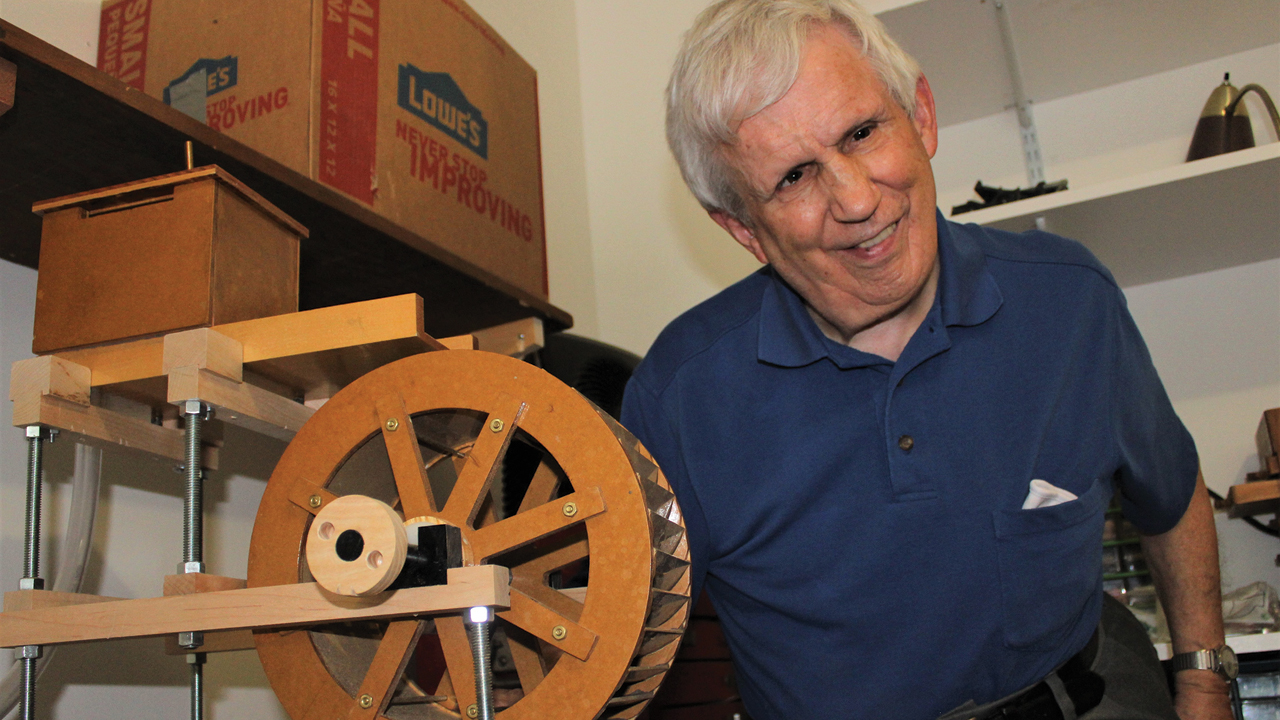 Dan Bowman displays his current project, a working model of a water-powered grist mill. — Jim Bishop