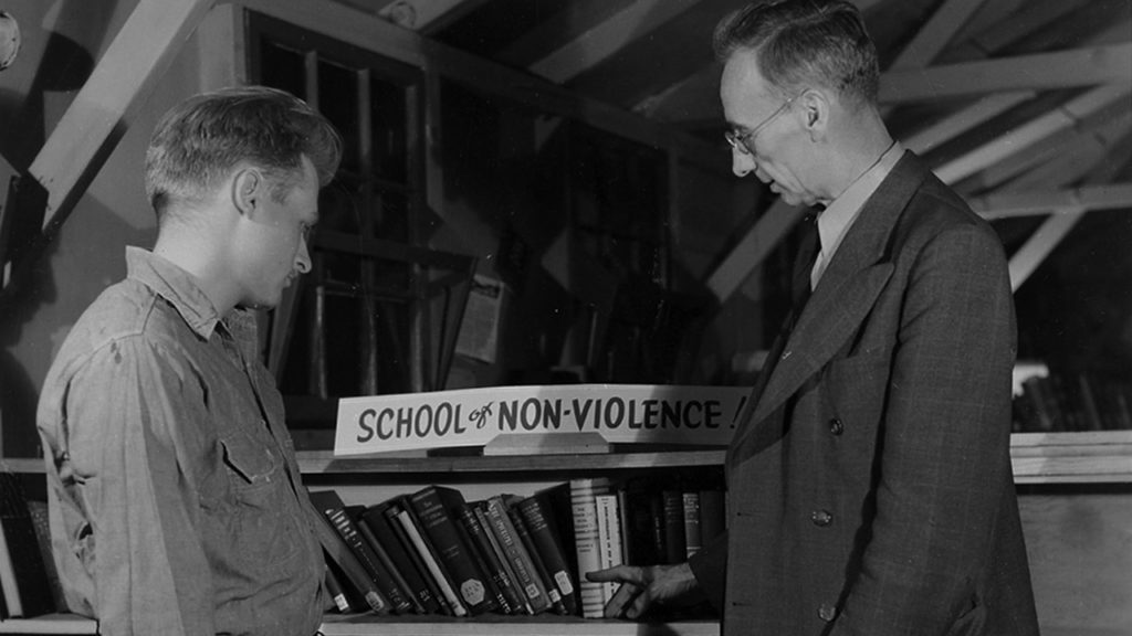 A.J. Muste, right, a leading Protestant pacifist clergyman and frequent visitor to CPS camps, inspects a collection of books on peace and nonviolence at Camp No. 52 in Powellsville, Md. — Center on Conscience and War Records, Swarthmore College Peace Collection