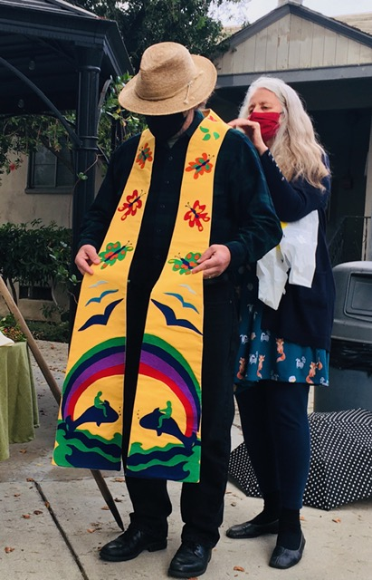Dr Karen McReynolds, Mark's spouse, presents stole, one of four gifts from the congregation—a staff, a small communion set for outdoor worship services, binoculars for vision, and this stole to symbolize Mark's witness. -- David Augsburger