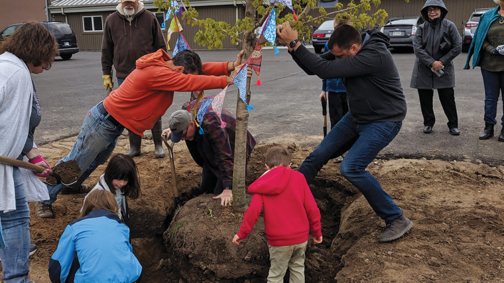 Children help plant one of more than 30 trees on May 12, 2019, during Assembly Mennonite Church's tree-planting service in Goshen, Ind. — Nadia Shank/Assembly Mennonite Church