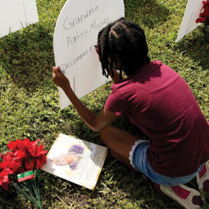 On Nov. 24, Kyla Harris, 10, writes a tribute to her grandmother Patsy Gilreath Moore, who died at age 79 of COVID-19, at a symbolic cemetery created to remember and honor lives lost to COVID-19 in the Liberty City neighborhood of Miami. — Lynne Sladky/AP