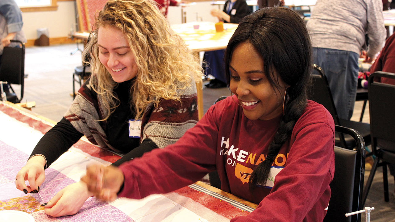 THIS WAS HOW WE PLANNED IT — Mennonite Central Committee's Great Winter Warm-up in January was one of the few MCC centennial events held as scheduled in 2020. Pictured are International Volunteer Exchange Program participants Gabriela Furman of Brazil and Nsofwa Kaseketi of Zambia working on a comforter in Kidron, Ohio. — Jennifer Steiner/MCC