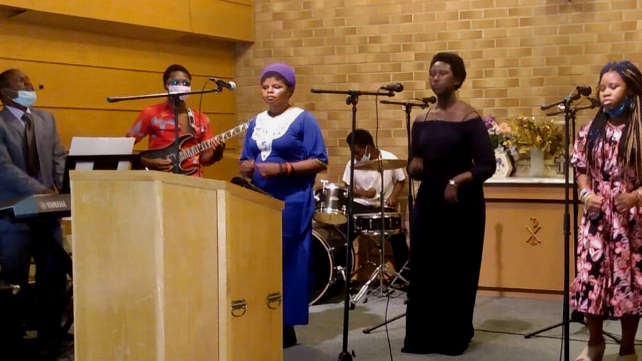 Masemo Wakibogo, left, leads worship at Amani Community Church in Wichita, Kan. — South Central Mennonite Conference