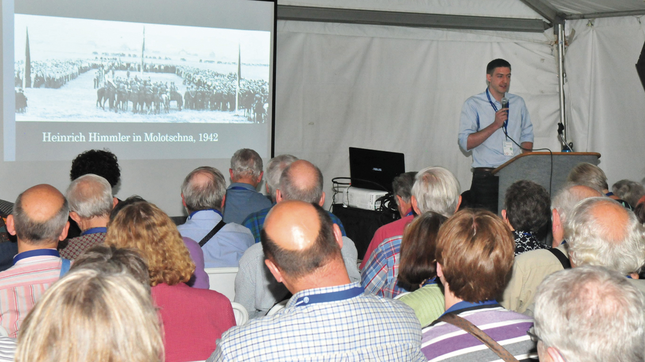 """Historian Ben Goossen shows a photo, """"Heinrich Himmler in Molotschna, 1942,"""" during his workshop, """"From Aryanism to Multiculturalism: Mennonite Ethnicity and German Nationalism, 1871 to Today"""" at the 2015 Mennonite World Conference Assembly in Harrisburg, Pa. — Dale D. Gehman for Meetinghouse"""