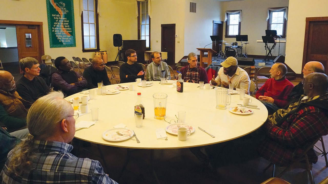 Juard Barnes, wearing a hat, shares his vision for a new ministry of reconciliation with Seeking the Beloved Community in 2018 at Fellowship of Hope. Herman Washington is at far left and Joe Sawatzky is center, in black sweater. — Keith Kingsley