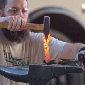 Michael Martin, founder and executive director of RAWtools, forms the metal of what used to be a gun into a hand-held garden tool in 2019 at Hesston College. — Larry Bartel/Hesston College