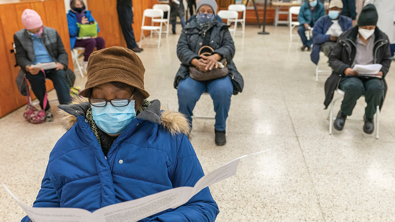 Elaine Chambers reads a coronavirus vaccination pamphlet while resting after receiving the first dose of the vaccine at a pop-up COVID-19 vaccination site at St. Luke's Episcopal Church on Jan. 26 in the Bronx borough of New York. — Mary Altaffer/AP