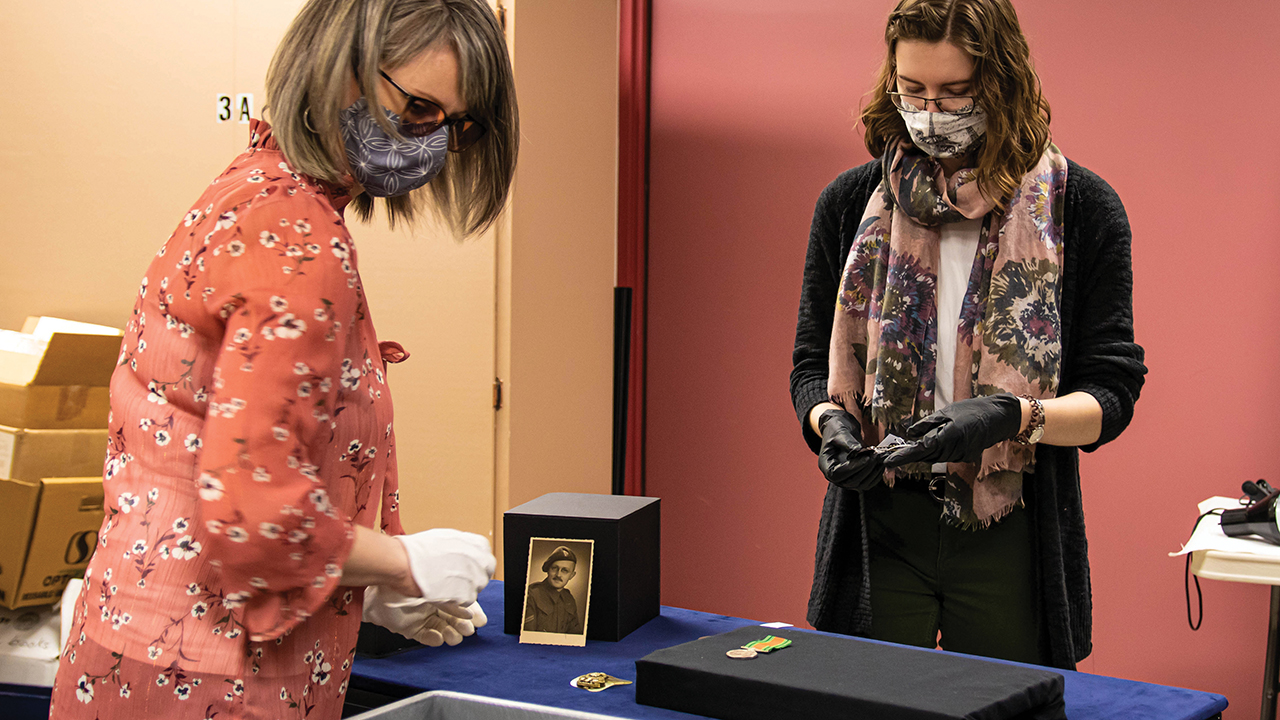 """Mennonite Heritage Village senior curator Andrea Klassen, left, and curatorial assistant Kara Suderman work on a display case featuring some of the artifacts that will be part of the """"Mennonites at War"""" exhibit. — Mennonite Heritage Village"""