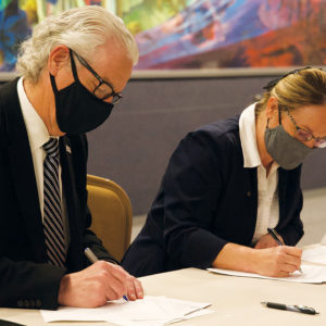 Malone University President David King, left, and Zollikon Institute director Norita Yoder sign an agreement about Zollikon Institute on March 17 at the Amish and Mennonite Heritage Center in Berlin, Ohio. — Malone University