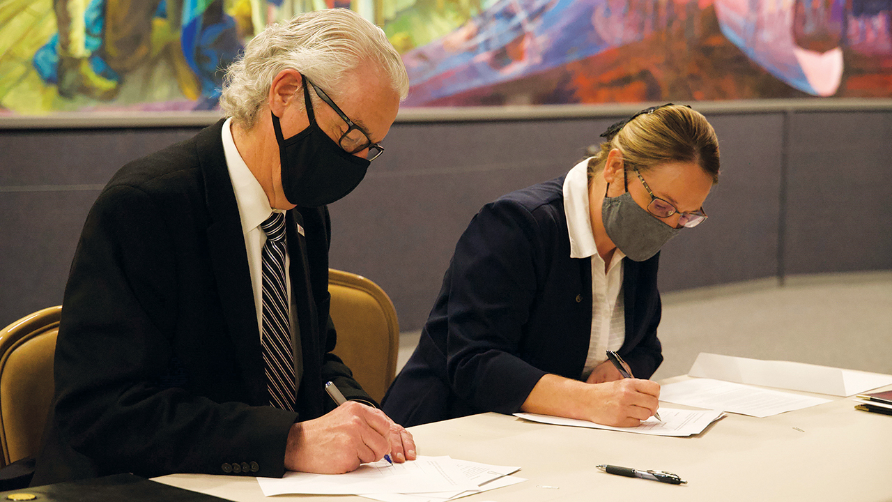 Malone University President David King, left, and Zollikon Institute director Norita Yoder sign an agreement about Zollikon Institute on March 17 at the Amish and Mennonite Heritage Center in Berlin, Ohio. — Malone University
