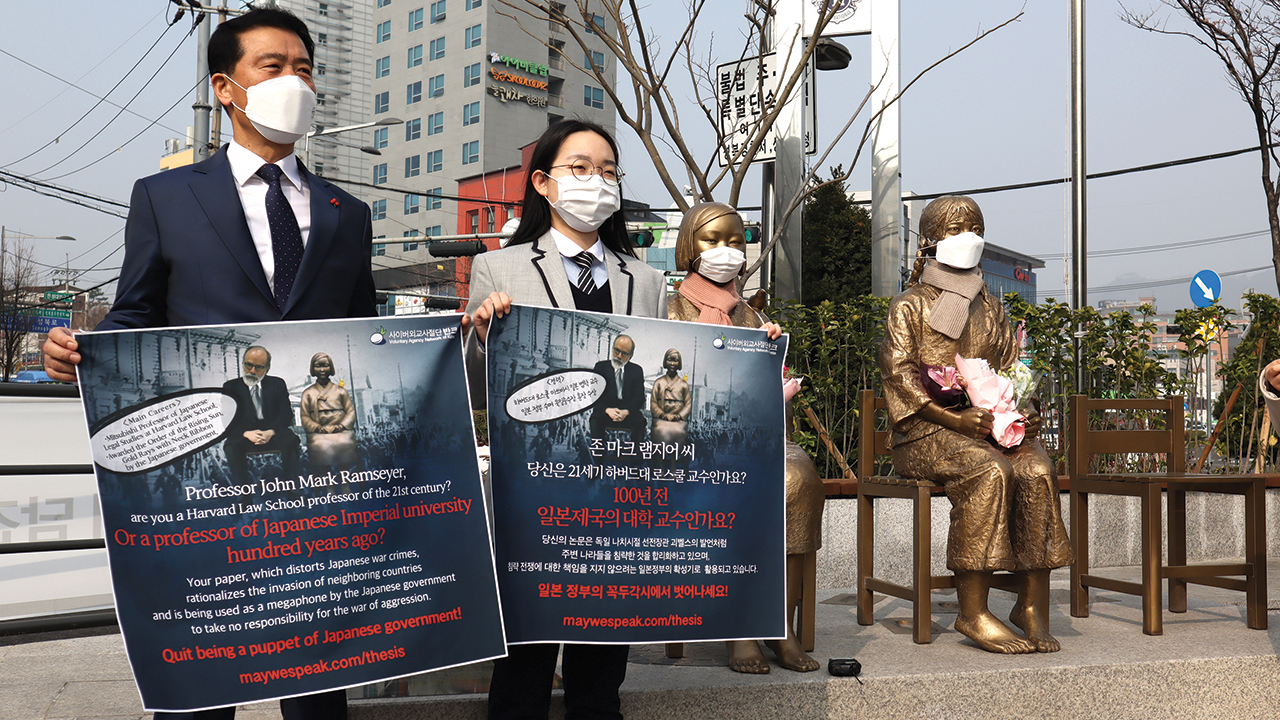 """Members of Voluntary Agency Network of Korea, an online organization of young people who share about their nation with people in other countries, hold a demonstration criticizing Harvard University professor J. Mark Ramseyer on March 15 at the Statue of Peace in Seoul, South Korea. Similar statues of """"comfort women"""" exist around the world. — Voluntary Agency Network of Korea"""
