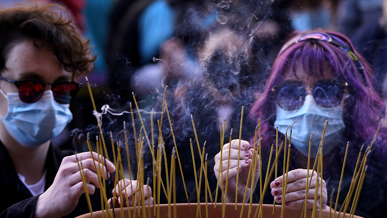 People leave incense sticks in a pot of rice to honor the victims of the Atlanta area massage parlors shootings during a memorial in Kansas City, Mo., March 28. The March 17 shootings at three Georgia massage parlors and spas that left eight people dead, six of them women of Asian descent, come on the heels of a recent wave of attacks against Asian Americans. Photo: Charlie Riedel/AP