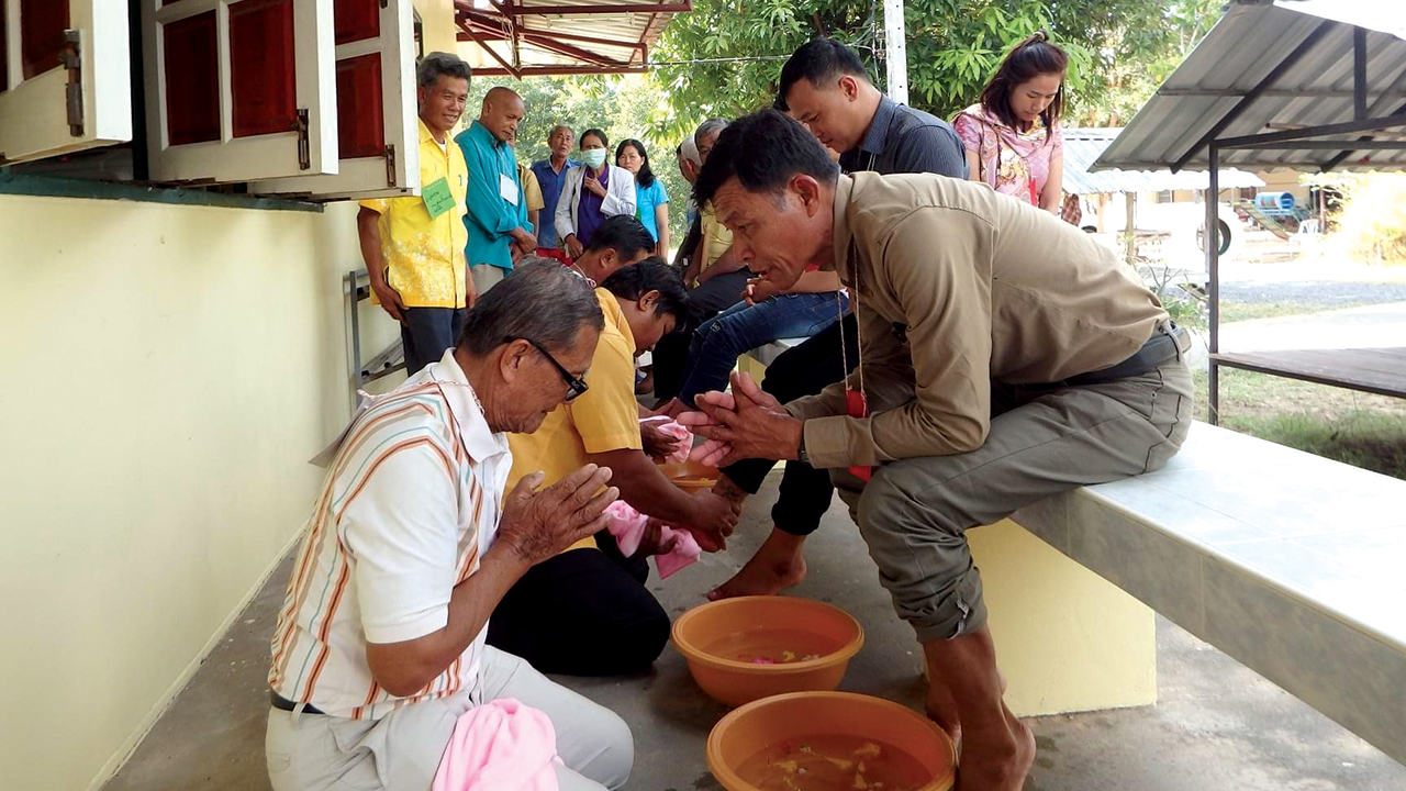 Sawang Phumewatthana, left, a lay leader of Sripuppa Living Water Church in Roi Et province, Thailand, prepares to wash the feet of Sa-nga Inchai, sitting on the bench. — Pat and Rad Houmphan