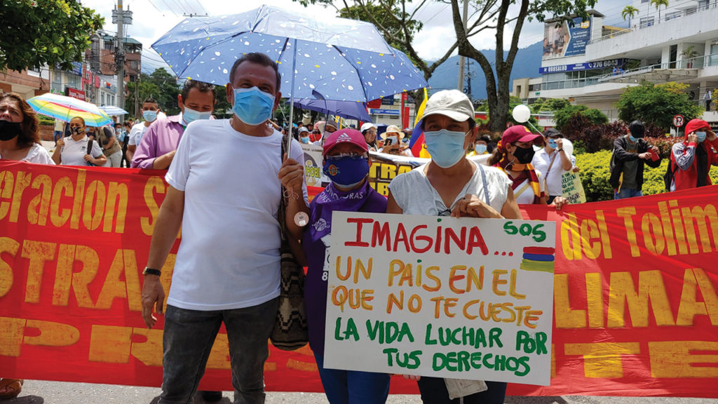 """Daniel Vargas, Pastor Amanda Valencia and Gloria Bastidas of the Mennonite Church of Mennonite Church of Ibagué march with the Human Rights Defense Committee of Tolima. The sign says, """"Imagine . . . a country where your life is not at risk when fighting for your rights. — Mennonite Church of Ibagué"""