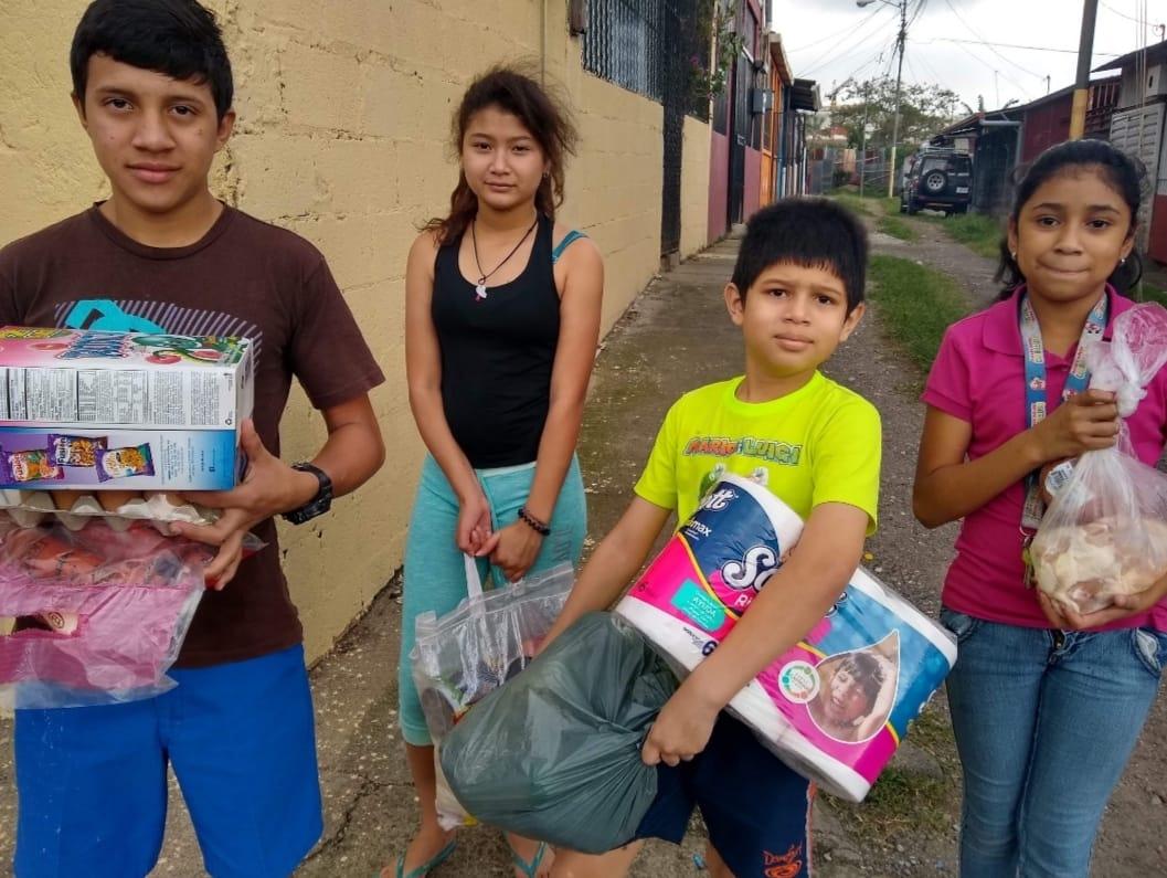 Grupo de niños de Guarari, Heredia Costa Rica recibiendo paquetes alimenticios de la Iglesias Menonita Discípulos de Jesús. Ashley, Anayanci, Sebastián, Geovani. Foto de Cindy Alpizar.