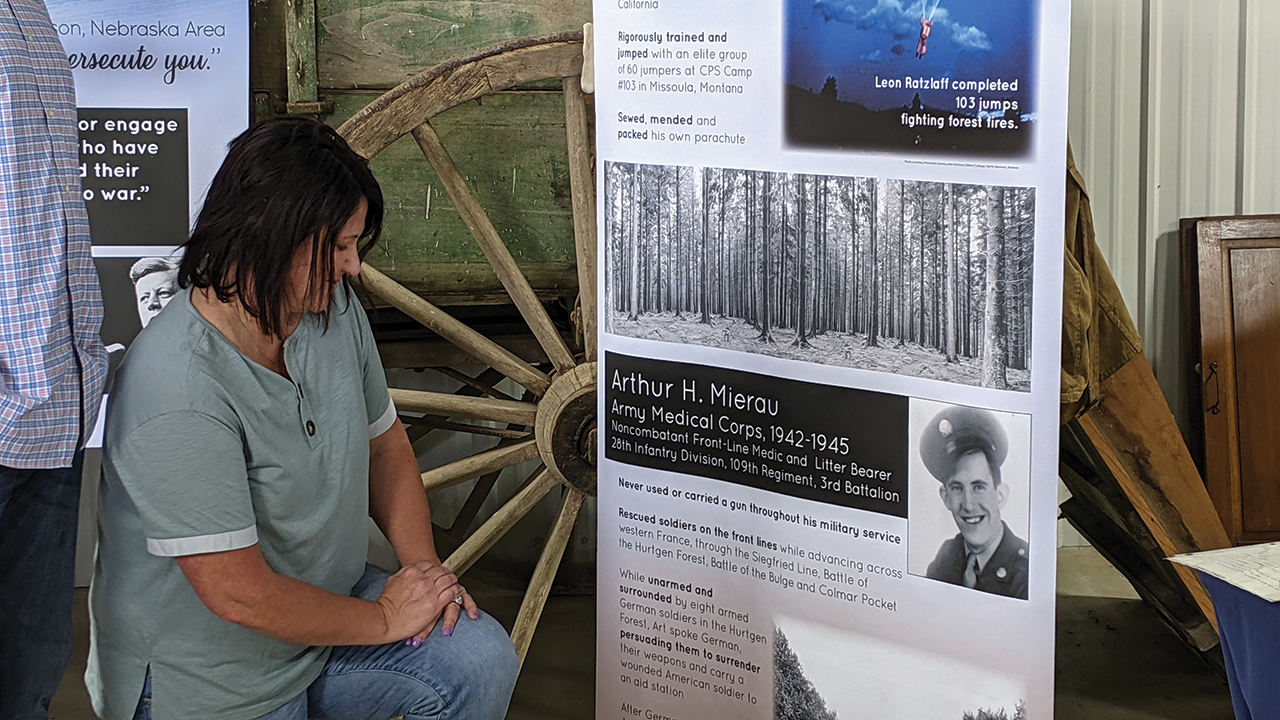 Dani Mierau Epp looks at a display about her grandfather Arthur Mierau, who received a Silver Star as a noncombatant medic and never touched a gun during his military service. On the front lines, he talked eight armed German soldiers into surrendering and carrying a wounded American soldier to his aid station. — Suzanne Freet Ratzlaff/Henderson Mennonite Heritage Museum and Park