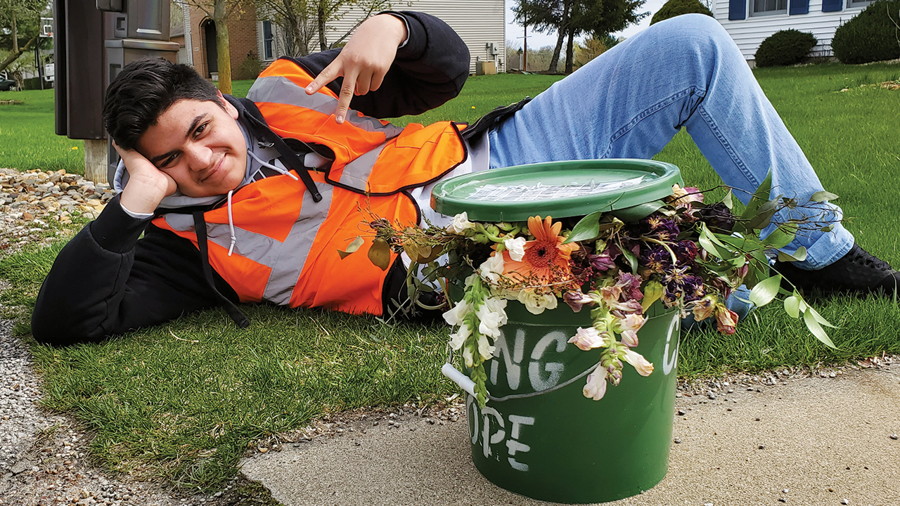 Jovan (identified only by his first name at his family's request) enjoys his work of weekly curbside food scrap pickup with a particularly attractive bucket. — Daniel Yoder