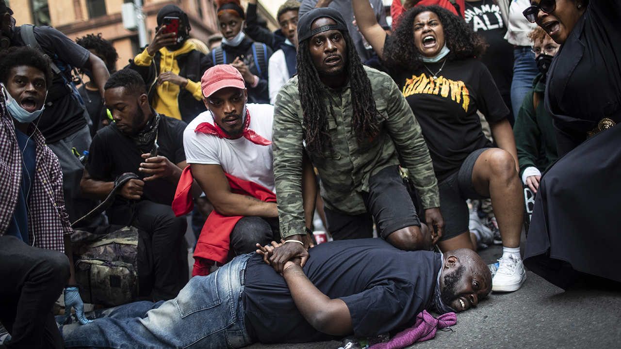 On June 2 in New York, protesters re-enact the scene where George Floyd was restrained by police. Floyd died after being restrained by Minneapolis police officers on May 25, 2020. — Associated Press