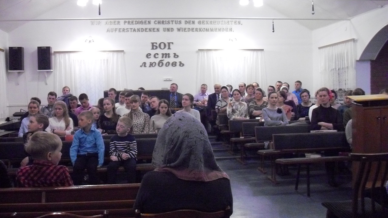 """Worshipers attend a service April 20 at the Mennonite Brethren church in Solntsevka, a community about 20 miles south of Apollonovka. The text on the wall reads """"God is love."""" — William Yoder"""