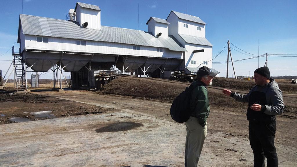 Jakob Dirksen, right, discusses Willock Farm's feed mill at Medvezhye with journalist William Yoder. — Reinhard Assmann