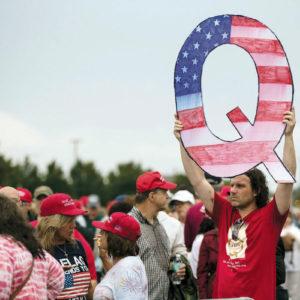 A man holds a QAnon sign. — Matt Rourke/AP