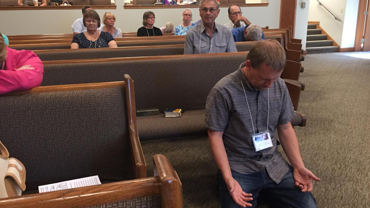 Delegate Corey Regehr prays during the South Central Mennonite Conference assembly July 24 in Hesston, Kan. — Paul Schrag/AW
