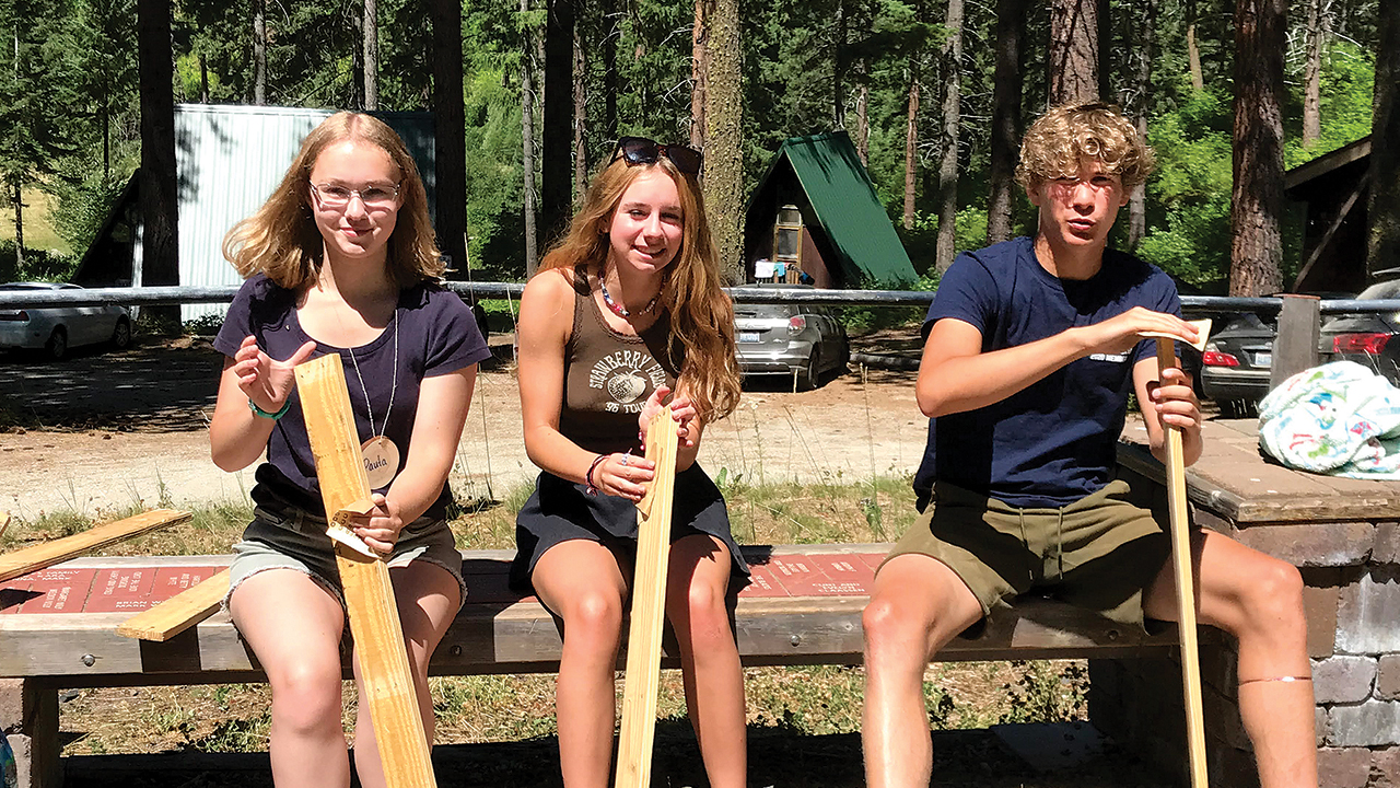 Youth from three Washington Mennonite congregations sand boards that will become a bench during a service project at their convention-themed high school retreat at Camp Camrec. — Amy Epp/Seattle Mennonite Church