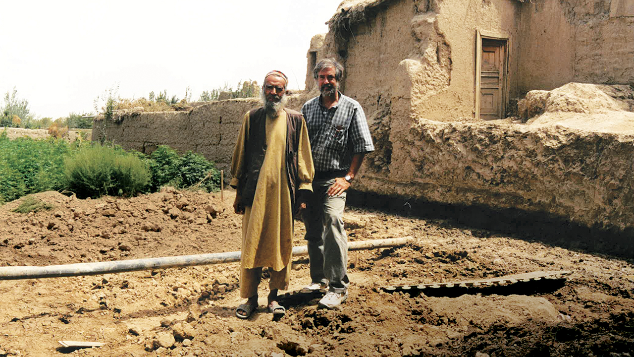 Abdul Hadi, pictured with Doug Hostetter in August 2002, returned to his home in Qala Kuja, Afghanistan, three years after it was destroyed in fighting between the Northern Alliance and the Taliban. Mennonite Central Committee and Church World Service helped him rebuild. — Doug Hostetter