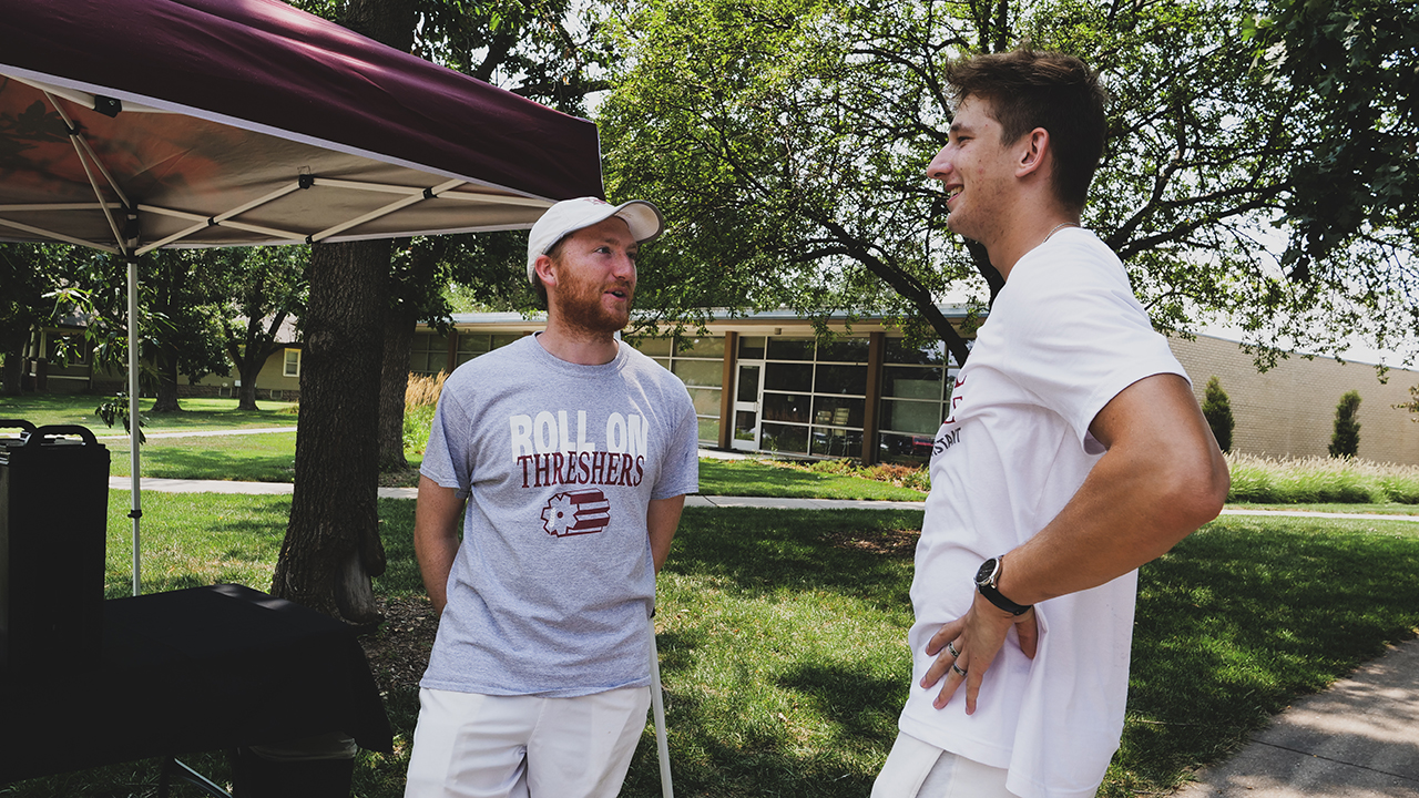 Bethel College tennis coach Gabe Johnson, left, talks to one of his players, Michael Cech, a sophomore from Modlany, Czech Republic, as students move into dorms. — Chase Dempsey/Bethel College