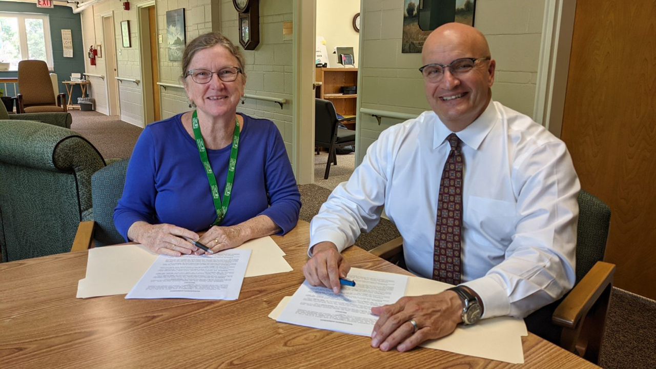 Mennonite Home Communities of Ohio board chair Elizabeth Kelly and John Warner, president and CEO of Brethren Retirement Community, sign management agreement documents. — Mennonite Home Communities of Ohio