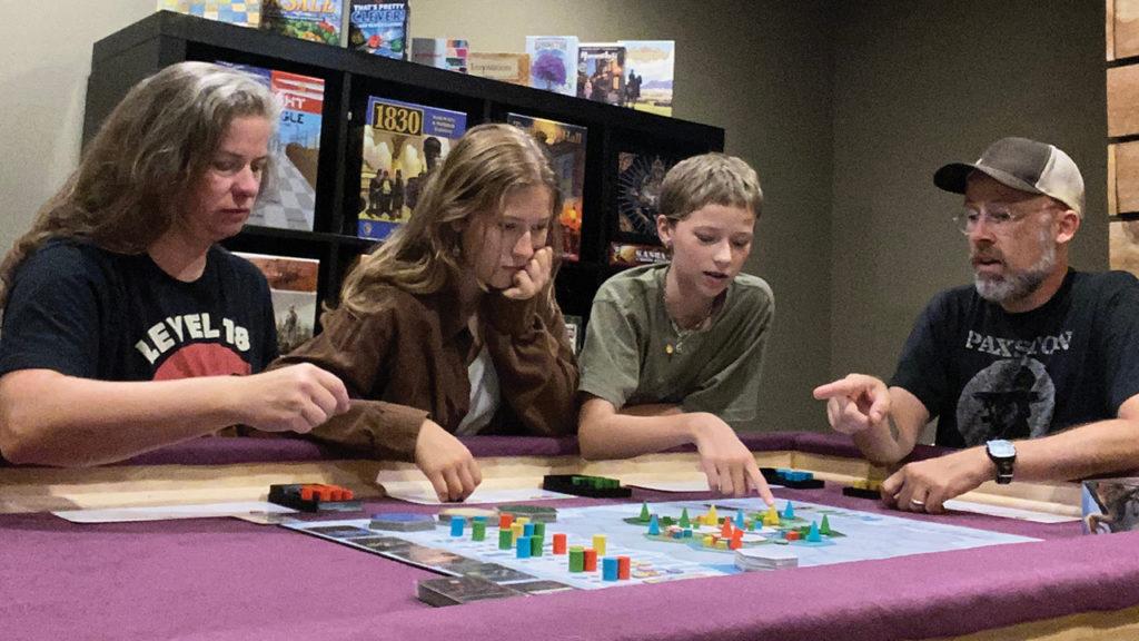 Kristin Green, Tona Ratigan Green, Siobhan Ratigan Green and John Ratigan play a board game in their Minneapolis home. — John Ratigan