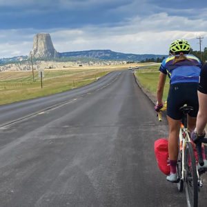 """Cyclists Joanna Friesen and Miriam Huebner approach Mato Tipila — """"Bear Lodge"""" in Lakota, also known as Devils Tower — in northeastern Wyoming on the Center for Sustainable Climate Solutions cross-country ride. — Sierra Ross Richer"""