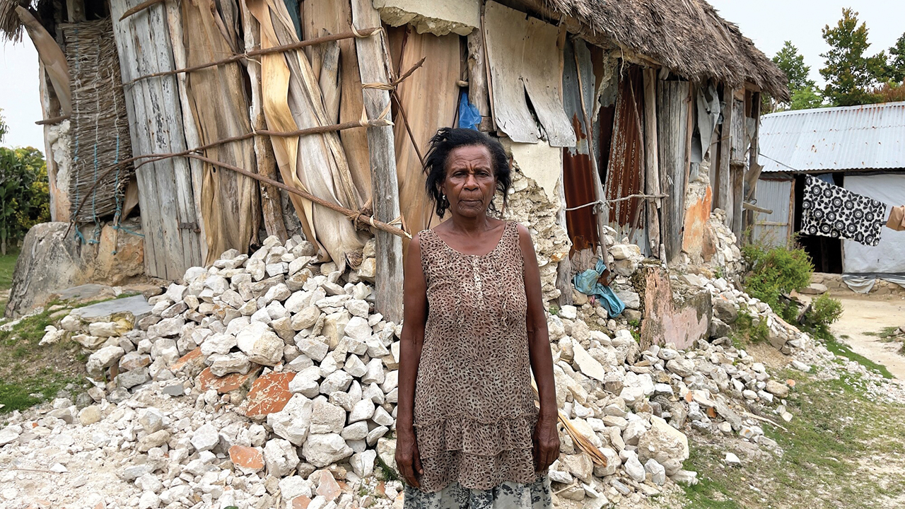 Prescione Roger stands in front of her home, which was destroyed by an earthquake in Saint-Jean-de-Sud, Haiti. — Paul Shetler Fast/MCC