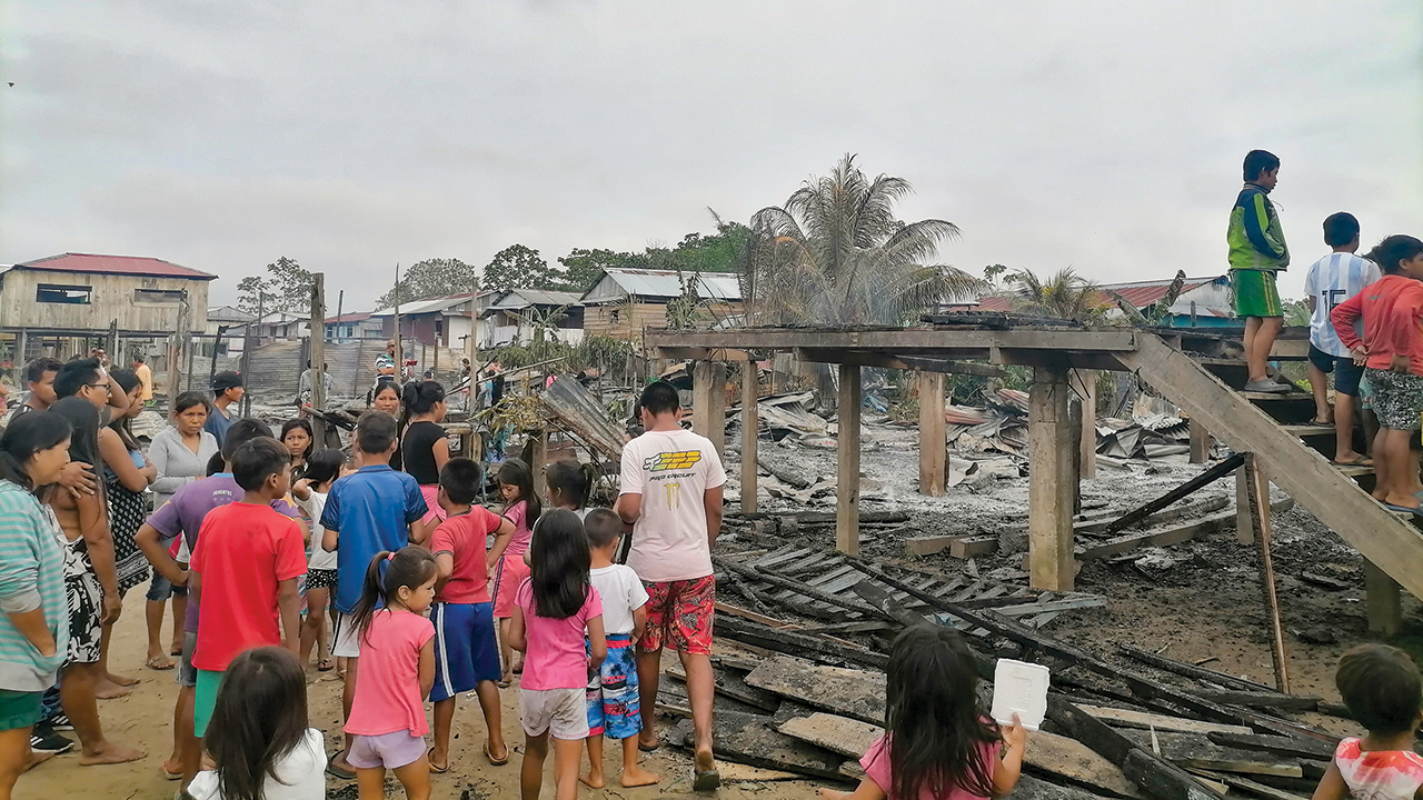 Adults and children on Isla Iquitos in Peru survey the damage at the site where their church and five houses burned to the ground Aug. 29. Children stand on the stairs that once led to their space for worship and learning. — Juan Carlos Moreno/MMN