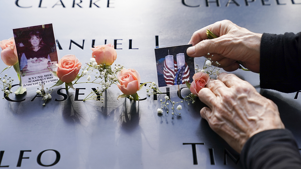 Mourners place flowers and pictures at the National September 11 Memorial and Museum on Sept. 11, 2020, in New York. — John Minchillo/AP