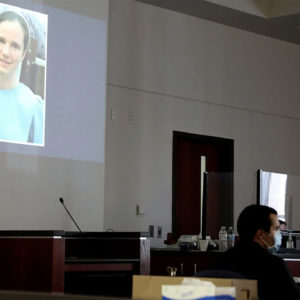Mark Gooch, 22, sits below an image of Sasha Krause shown on a screen during his trial at the Coconino County Superior Court in Flagstaff, Arizona, on Sept. 24. Gooch was charged with first-degree murder in Krause's death in early 2020. — Jake Bacon/Arizona Daily Sun via AP